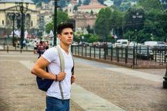 Hübscher junger Mann, der in europäischen Stadtplatz geht Stockfotos