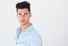 Hübscher junger Mann, der gegen weißen Hintergrund aufwirft Stockfotos