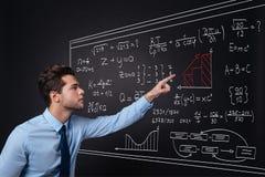 Hübscher junger Mann, der Gleichungen darstellt Stockfoto