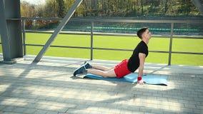 Hübscher junger Mann, der Kniesehnen-Ausdehnungs-Übung auf Mat At Stadium tut Füße liegen auf dem Teppich-Nachdruck auf stock video footage