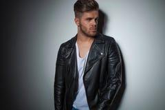 Hübscher junger Mann in der Lederjacke schaut, um mit Seiten zu versehen Stockbilder
