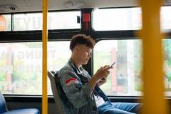 Hübscher junger Mann, der mit dem Bus reist und eine digitale Tablette verwendet Stockfotos