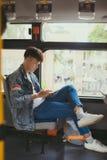 Hübscher junger Mann, der mit dem Bus reist und eine digitale Tablette verwendet Lizenzfreie Stockbilder