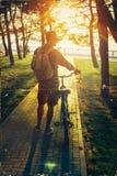 Hübscher junger Mann, der mit Fahrrad im Sommer-Park bei Sonnenuntergang, hintere Ansicht-Feiertags-Wochenenden-Tätigkeit geht Lizenzfreies Stockfoto