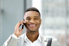 Hübscher junger Mann, der mit Handy lächelt Lizenzfreies Stockbild