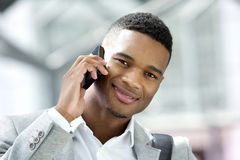 Hübscher junger Mann, der mit Mobiltelefon lächelt Stockfotos