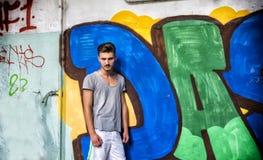 Hübscher junger Mann, der nahe bei Graffiti lächelt Lizenzfreie Stockfotografie