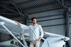 Hübscher junger Mann, der nahe smal Flugzeug steht stockbild