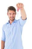 Hübscher junger Mann, der Schlüssel des neuen Hauses zeigt Stockbild