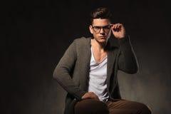 Hübscher junger Mann, der seine Gläser repariert Stockfotografie