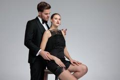Hübscher junger Mann, der seine Sitzfreundin von hinten umfasst lizenzfreies stockfoto