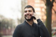 Hübscher junger Mann, der an seinem Telefon in einem Stadtgebiet spricht Stockfoto