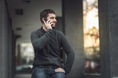 Hübscher junger Mann, der an seinem Telefon in einem Stadtgebiet spricht Lizenzfreie Stockfotos