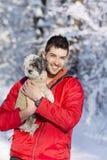 Hübscher junger Mann, der seinen kleinen weißen Hund im Winter umarmt snowing lizenzfreies stockbild