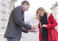 Hübscher junger Mann, der seiner Freundin eine Geschenkbox bei der Stellung gibt Lizenzfreie Stockbilder