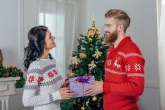 hübscher junger Mann, der seiner schönen Freundin Weihnachtsgeschenk gibt lizenzfreies stockbild