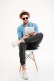 Hübscher junger Mann, der Tablette verwendet und auf dem Stuhl sitzt Lizenzfreies Stockfoto