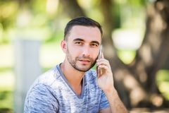Hübscher junger Mann, der am Telefon beim Sitzen auf Bank im Park spricht lizenzfreie stockfotografie