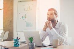 Hübscher junger Mann, der am Tisch im hellen Büro und im drea sitzt lizenzfreie stockfotografie