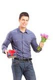 Hübscher junger Mann, der Tulpen und Geschenkbox hält Stockfoto