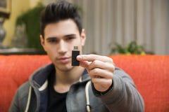 Hübscher junger Mann, der USB-Schlüssel in seiner Hand zeigt lizenzfreies stockfoto