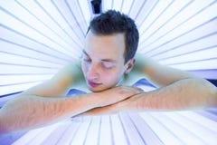 Hübscher junger Mann, der während einer bräunenden Sitzung sich entspannt Lizenzfreies Stockfoto