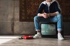 hübscher junger Mann in der Weinlese kleidet das Sitzen auf Retro- Fernseher nahe Rot verdrahtetem Telefon vor dem Wolldeckenhäng lizenzfreie stockfotos