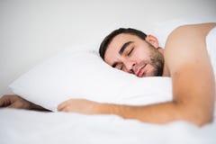 Hübscher junger Mann, der zu Hause im weißen Bett an seinem Raum schläft stockfoto