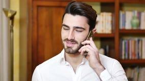 Hübscher junger Mann, der zu Hause am Telefon spricht stock video footage