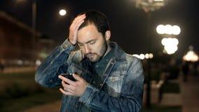 Hübscher junger Mann, entsetzt, überrascht mit Textnachricht stockfotografie