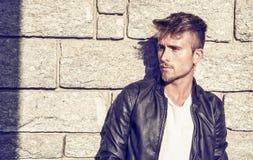 Hübscher junger Mann gegen Steinwand Stockbilder