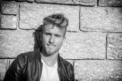 Hübscher junger Mann gegen Steinwand Stockfotografie