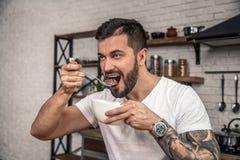 Hübscher junger Mann hat seine Frühstückskost aus Getreide mit Milch er genießt das Frühstückslächeln lizenzfreie stockbilder