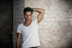 Hübscher junger Mann im Altbau gegen Backsteinmauer Stockbilder