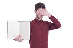 Hübscher junger Mann im Hemd, das Notizbuchkopienraum hält Stockfotografie