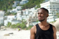 Hübscher junger Mann im schwarzen Hemd, das am Strand steht Lizenzfreies Stockbild