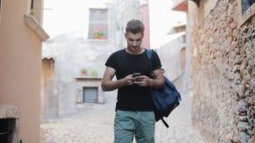 Hübscher junger Mann im schwarzen T-Shirt und mit Rucksack gehend in die alte Stadt und Smartphone verwendend stock video
