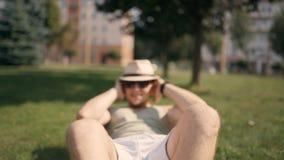 Hübscher junger Mann im T-Shirt und in den kurzen Hosen pumpt die Presse auf dem Park draußen Betrachten der Kamera und Lächeln stock video