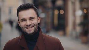Hübscher junger Mann im zufälligen braunen Mantel, der im Stadtzentrum steht und hell in Richtung zur Kamera lächelt Spaß haben stock footage
