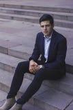 Hübscher junger Mann mit dem angeredeten Haar Der Mann sitzt auf den Schritten Stockfotos