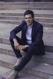 Hübscher junger Mann mit dem angeredeten Haar Der Mann sitzt auf den Schritten Lizenzfreie Stockfotos