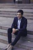 Hübscher junger Mann mit dem angeredeten Haar Der Mann sitzt auf den Schritten Stockfoto