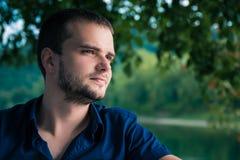 Hübscher junger Mann mit dem Bart, der eine Seite schaut stockbilder