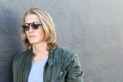 Hübscher junger Mann mit dem blonden langen Haar und der Sonnenbrille lokalisiert auf grauem Hintergrund Art und Weisestudioschuß Lizenzfreie Stockfotos