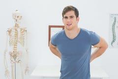 Hübscher junger Mann mit den Rückenschmerzen, die im Büro stehen Stockfoto