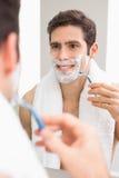 Hübscher junger Mann mit der Reflexion, die im Badezimmer rasiert lizenzfreie stockfotos