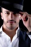 Hübscher junger Mann mit einem Hutschwarzhintergrund Stockfoto