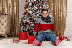 Hübscher junger Mann mit einem Schal, der mit Geschenken auf Plaid nahe dem Weihnachtsbaum sitzt stockfotografie
