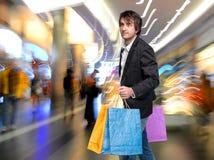 Hübscher junger Mann mit Einkaufstaschen Stockbild