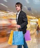 Hübscher junger Mann mit Einkaufstaschen Stockfotos